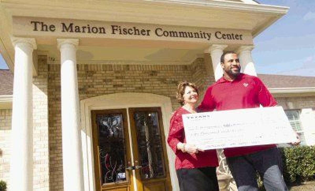 Marion Fischer, left, is presented a $50,000 check for the Montgomery County Women's Center by Houston Texans offensive linemen Duane Brown before a ceremony honoring her community work Thursday. Fischer was selected as the 2014 Houston Texans Community Quarterback grand prize winner in recognition for her community involvement with the Montgomery County's Women's Center. Go to HCNpics.com to view more photos from the award ceremony.