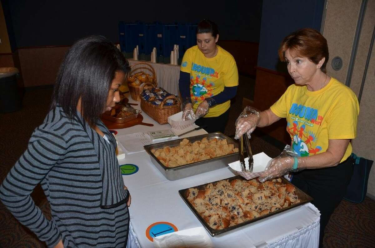 CFISD food service employees Araceli Nunez, left, and Lesha Ranjel serve samples of muffins for guests at the Annual Food Tasting on Friday at the Berry Center.