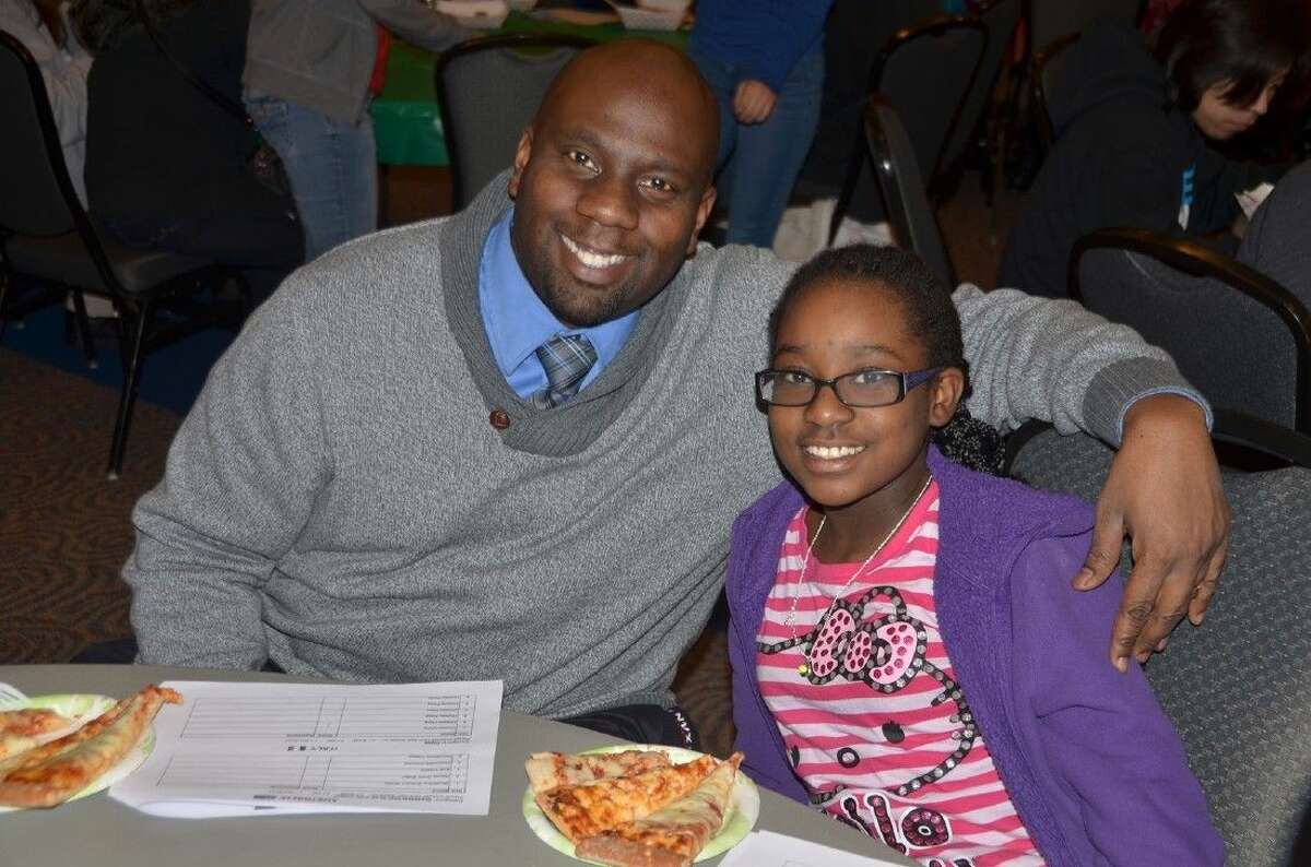 Campbell Middle School assistant principal Plas Williams and his daughter, Campbell sixth-grade student Ayana Williams, sample the pizza options at the Annual Food Tasting.