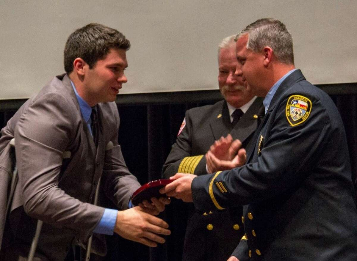 During the College of the Mainland Fire Academy graduation, COM instructors Greg Obert, right, and Stan Kozlowski, center, presented student Austin Brinkley with the Instructors' Award.