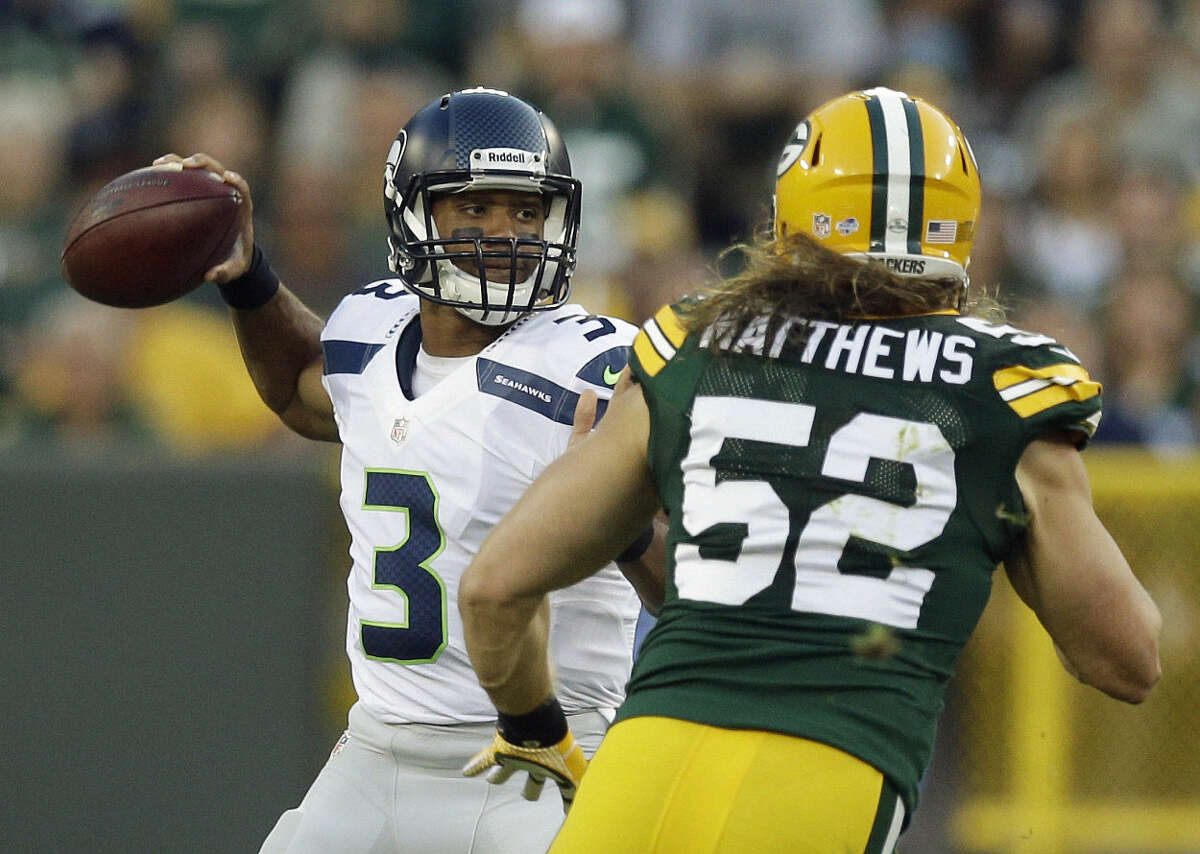 FILE - In this Aug. 23, 2013, file photo, Seattle Seahawks quarterback Russell Wilson tries to avoid the rush of Green Bay Packers outside linebacker Clay Matthews (52) during the first half of an NFL preseason football game in Green Bay, Wis. The Seahawks and Packers meet in the NFC Championship Sunday, Jan . 18, 2015, in Seattle. (AP Photo/Morry Gash, File)