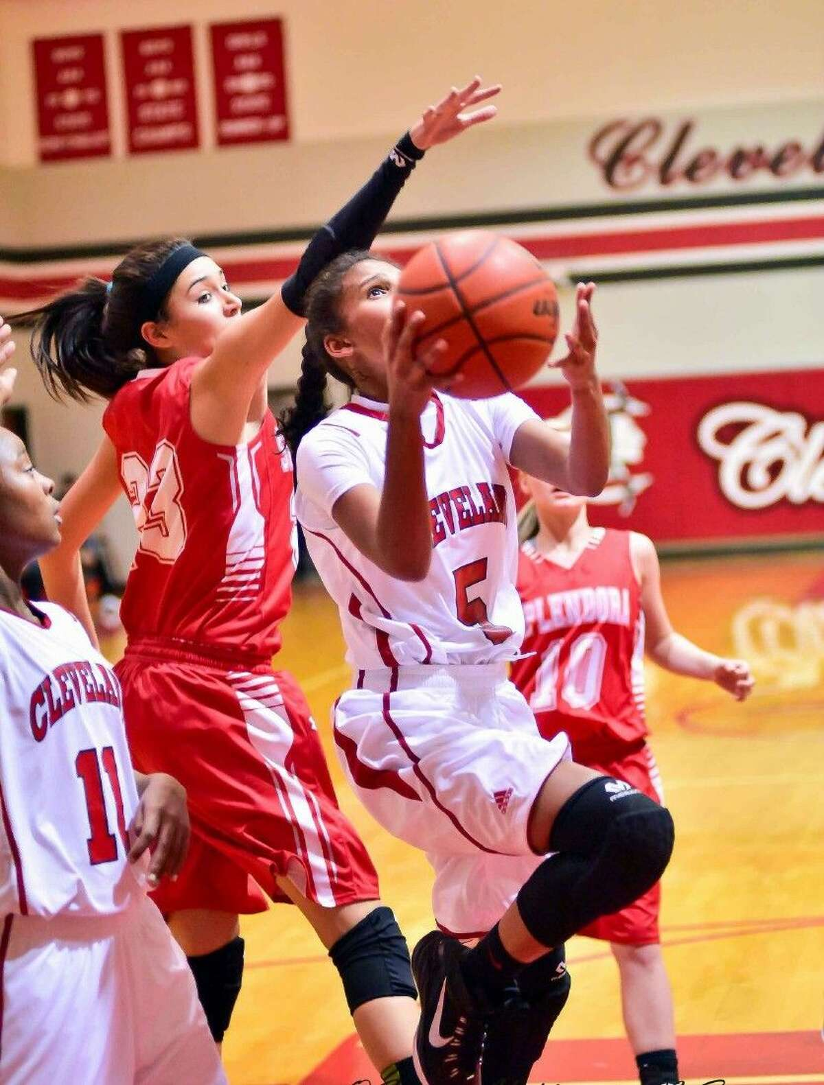 Simran Mayfield shoots for Cleveland with Splendora's Zoe O'Steen reaching for the block, Jan. 13, 2015.