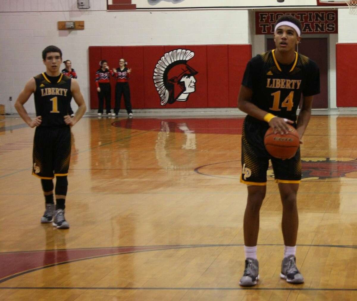 Trevor Pierce (1) of the Liberty Panthers watches as Darien Mallet (14) prepares to make a free throw.