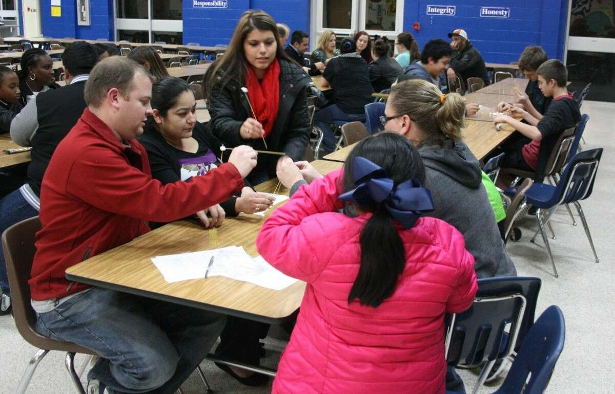 Parents and children divide up into groups for a challenge that requires them to cooperate and build a tower together during Shepherd Middle School's Creating Alliances meeting.