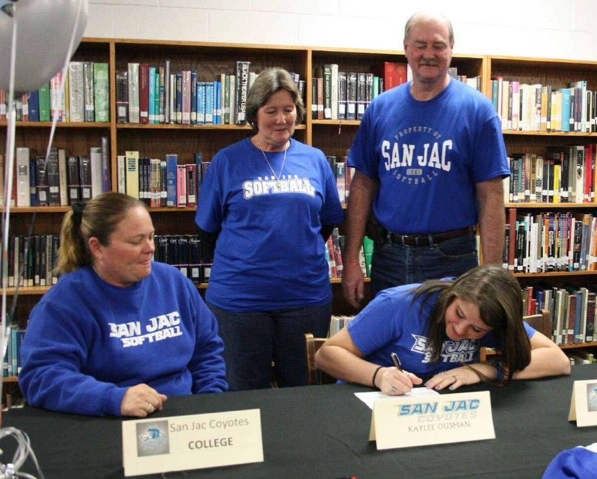 Lady Trojan varsity softball pitcher Kaylee Ousman (front right) signs on with the San Jacinto College Coyotes next to Coach Kelly Saenz (left). Her parents, Bridgette and Rick Ousman (back row) watch excitedly behind their daughter.