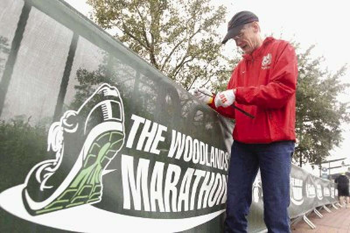 Steve Smith helps tie a sign in preparation for The Woodlands Marathon today. Approximately 8,000 runners are expected to participate in the marathon, half marathon, marathon relay, 5K run and 2k family fun run and walk.