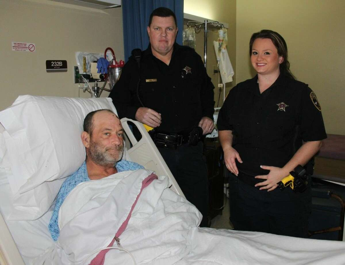 Sitting in a hospital bed at Liberty-Dayton Regional Medical Center, Tarkington resident James Gray is reunited with the two Liberty County sheriff's deputies, Kenneth Taylor and Stephanie Walden, who are credited with saving his life. Gray went missing around 11 p.m. Sunday, Jan. 11, and was discovered in a wooded area four hours later by the sheriff's deputies.