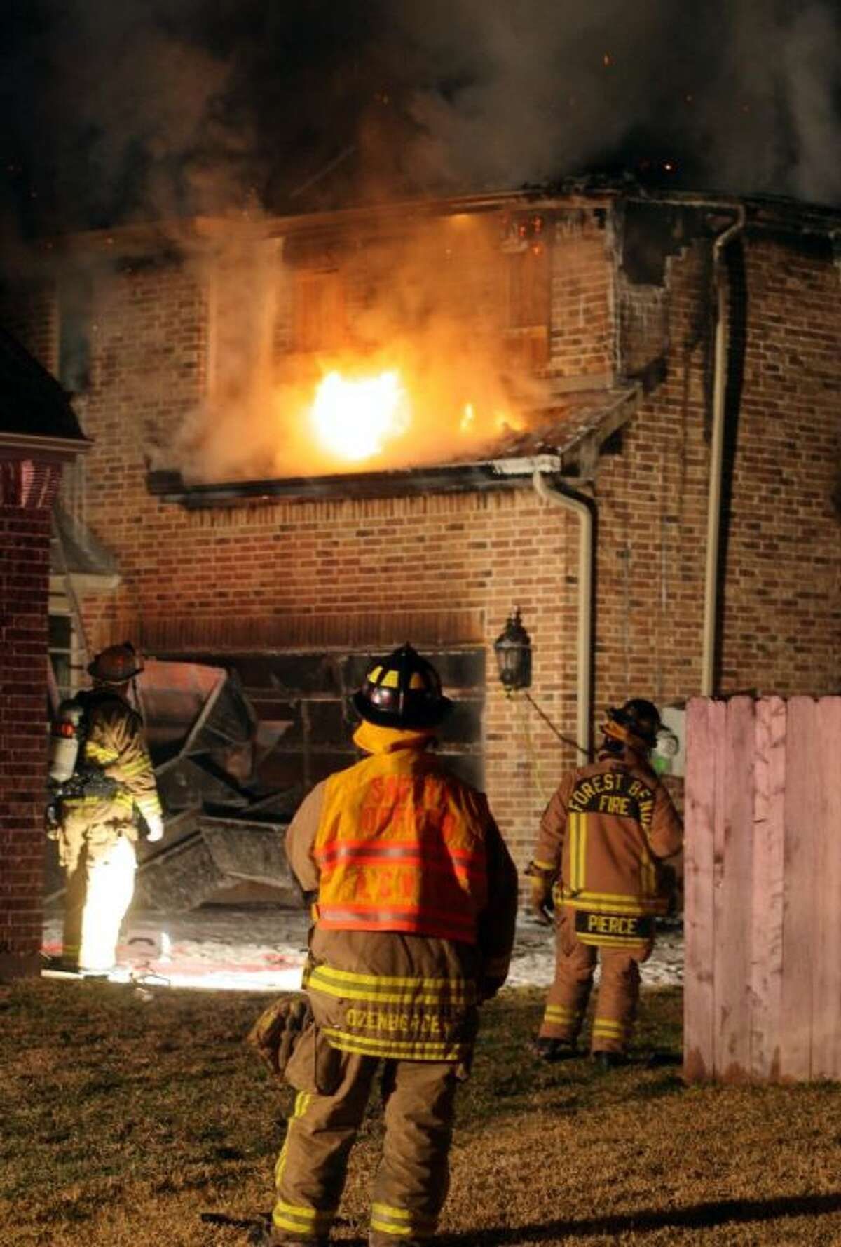 Firefighters outside the house monitor the fire as inside crews locate and extinguish the fire.