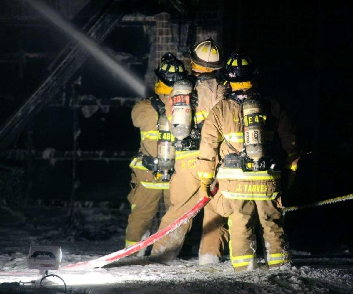 Firefighters use foam to battle the fire.