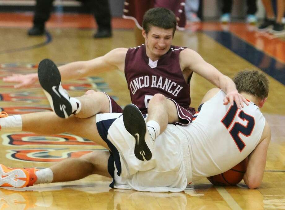 Cinco Ranch's J.R. Adams falls over Seven Lakes' Ben Gautschy during their Jan. 9 game at Seven Lakes High School in Katy. To view or purchase this photo and others like it, go to HCNPics.com. Photo: Alan Warren
