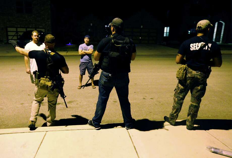 """An """"Armed Voluntary Security Detail"""" consisting of homeowners in the Cobblestone neighborhood show how they typically patrol the neighborhood on foot on Wednesday, Sept. 28, 2016. The patrol on Wednesday was Brian (from left), Mike and Daniel who were chatting with homeowners Robert (left) and Moses. The patrol was formed after crimes in the neighborhood alarmed some homeowners. They carry rifles and handguns along their patrols. (Kin Man Hui/San Antonio Express-News) Photo: Kin Man Hui, Staff / San Antonio Express-News / ©2016 San Antonio Express-News"""