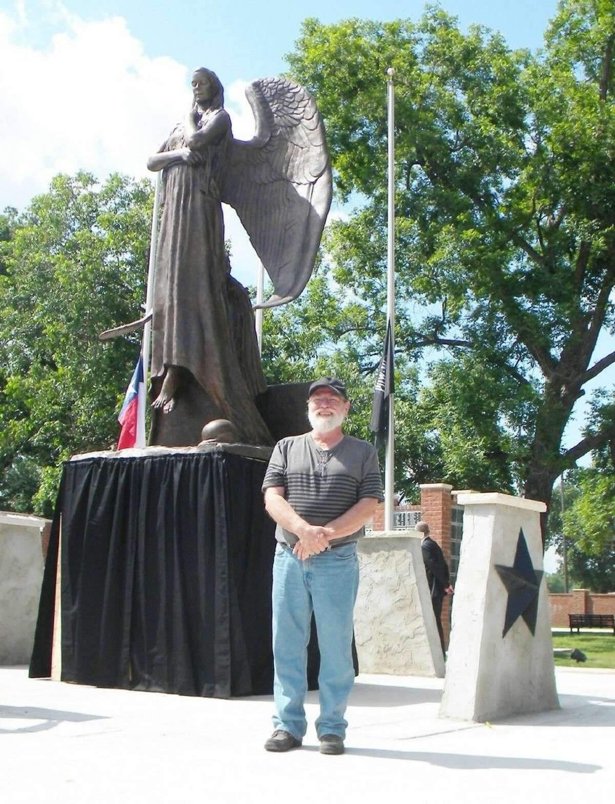 Bill McGlaun stands before a 17-foot tall angel he created to honor the nation's fallen service personnel. The angel is located in Smithville, Texas.