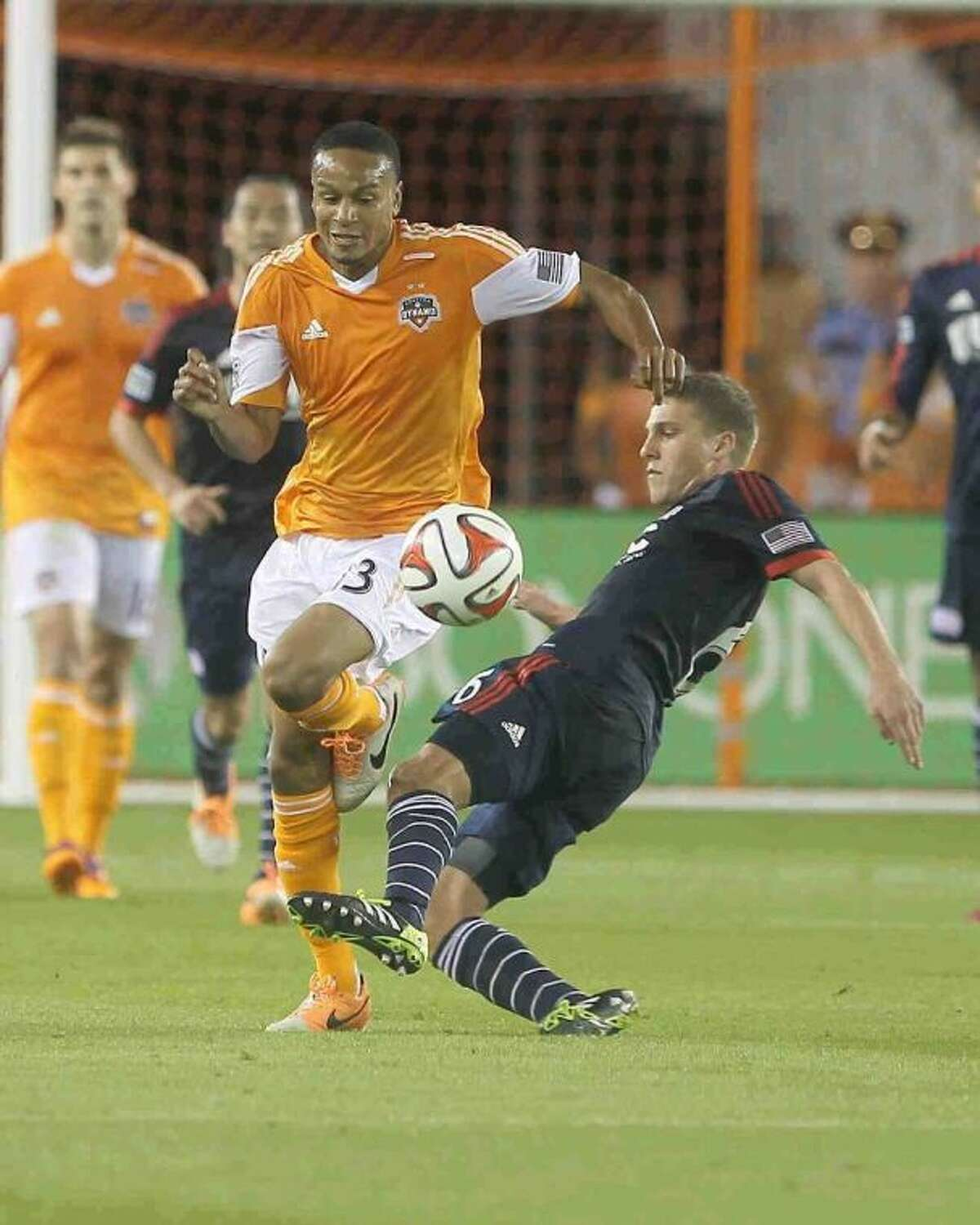 New England Revolution midfielder Scott Caldwell (6) goes for the ball against Houston Dynamo midfielder Ricardo Clark (13) during the first half of an MLS soccer game Saturday. The Dynamo won 4-0.