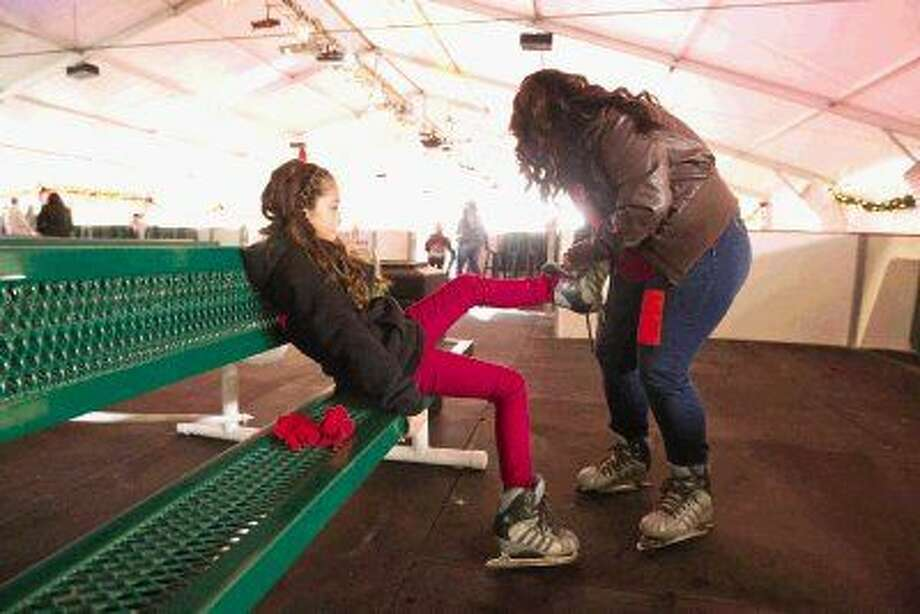 In this 2014 file photo, Emery Hidalgo gets some help with her skates from her mom, Sondra, before ice skating at The Woodlands Ice Skating Rink near The Woodlands Mall. Photo: Jason Fochtman