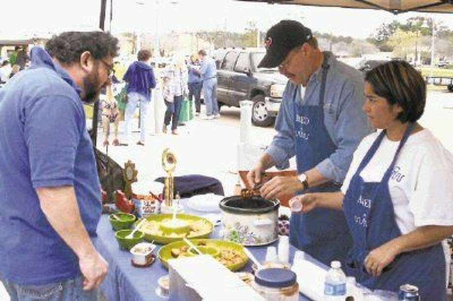 Volunteers with the White Water Cowboy BBQ Company help serve chili samples at a past HAAM Raise the Roof Chili Cook-off.