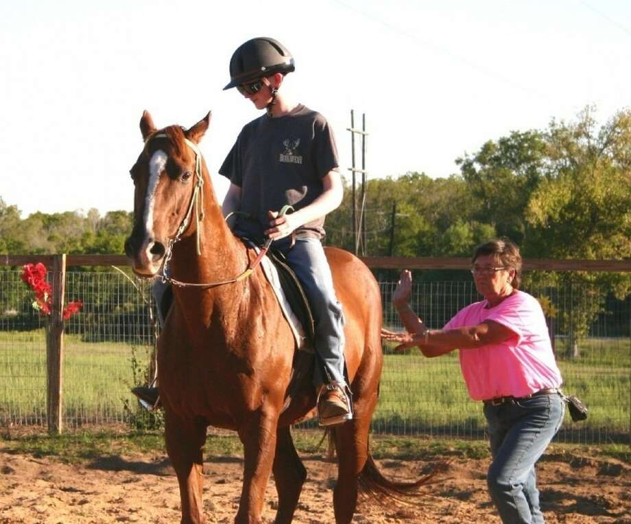 Donna Wiebelhaus, executive director of the SpiritHorse Therapeutic Riding Center of Liberty, gives Kyle's horse, Vern, a giddyup during a riding lesson.