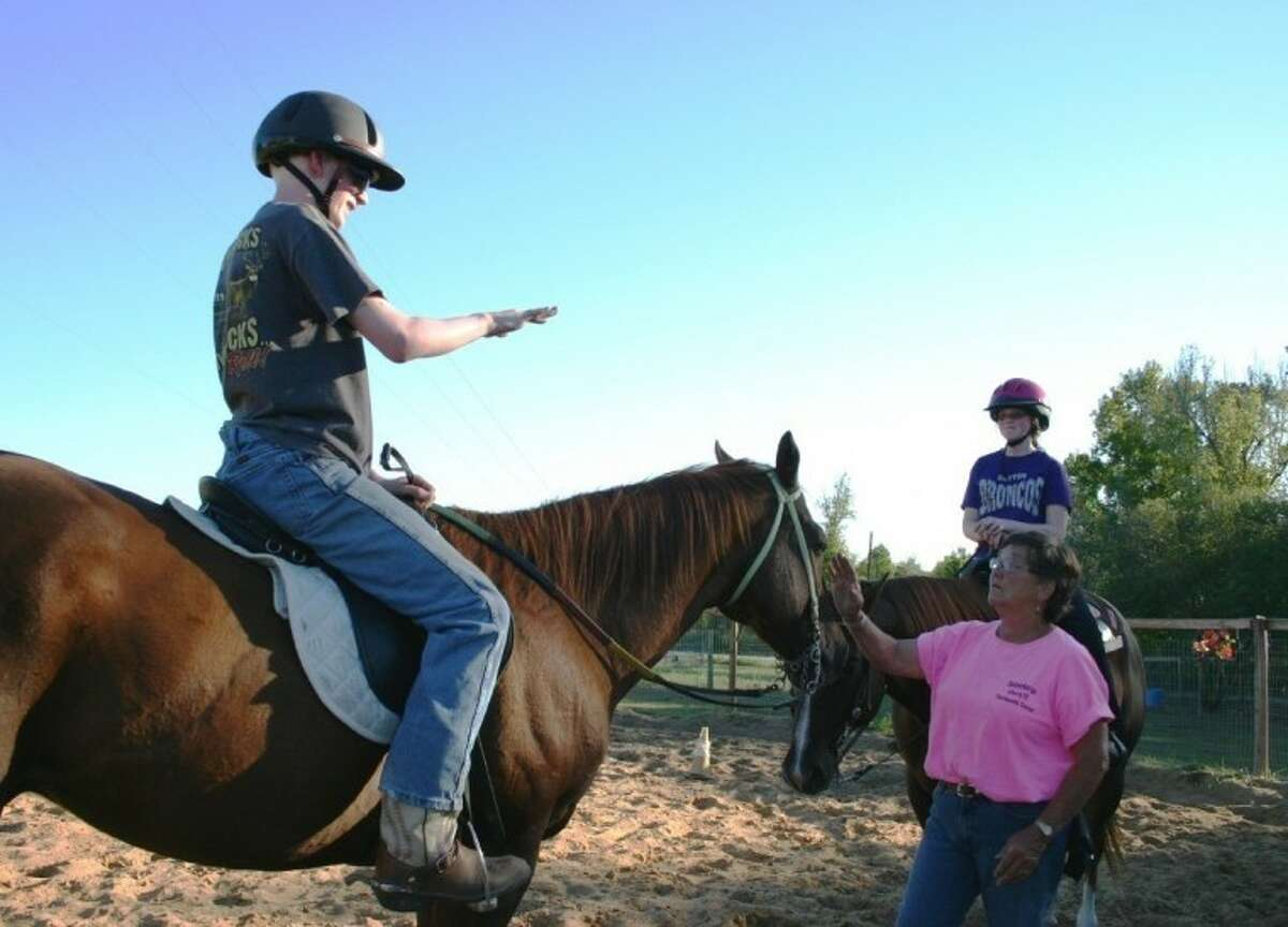 Donna Wiebelhaus, executive director of the SpiritHorse Therapeutic Riding Center of Liberty, conducts a riding lesson for Kyle and his sister, Amanda.