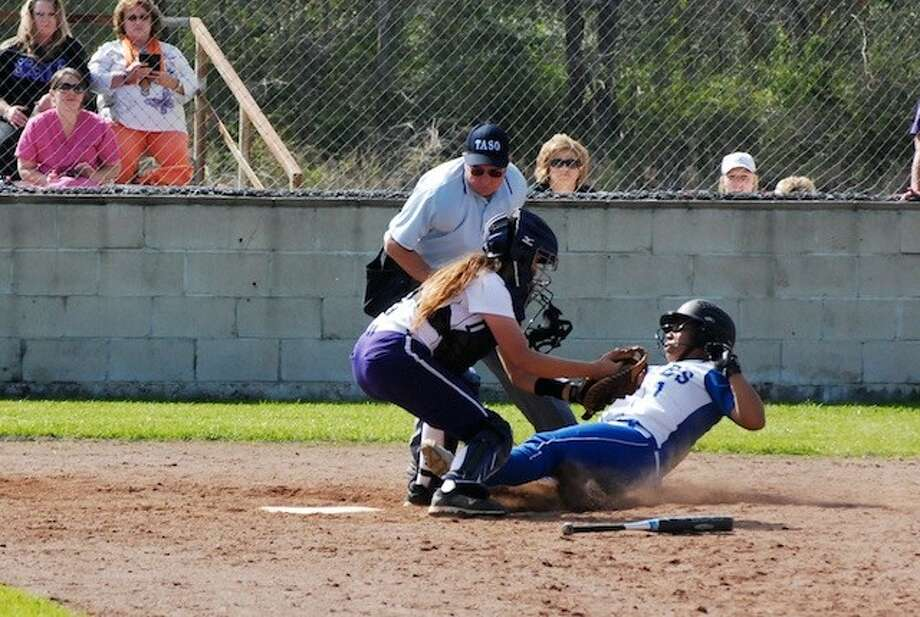 Chelsey Caldwell slid into home between the legs of catcher Alicia Davila, The umpire called her safe, giving Barbers Hill the lead in a game that went through five extra innings Monday afternoon, March 10. Photo: CASEY STINNETT / Houston Community Newspapers, 2014