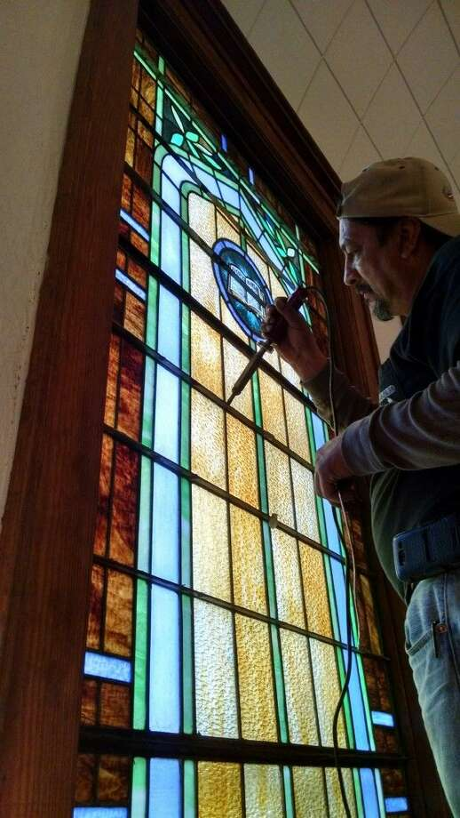 Joel Vigil of Freebird Glass Inc. of Cypress, Texas, solders a section of a stained glass window at First United Methodist Church in Cleveland. The windows are being repaired as part of an overall restoration of the church. Photo: Submitted