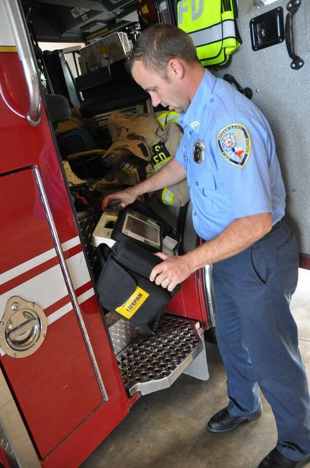 Firefighter Victor Peschke inspects the Automated External Defibrillator (AED) equipment before loading it into the fire truck.