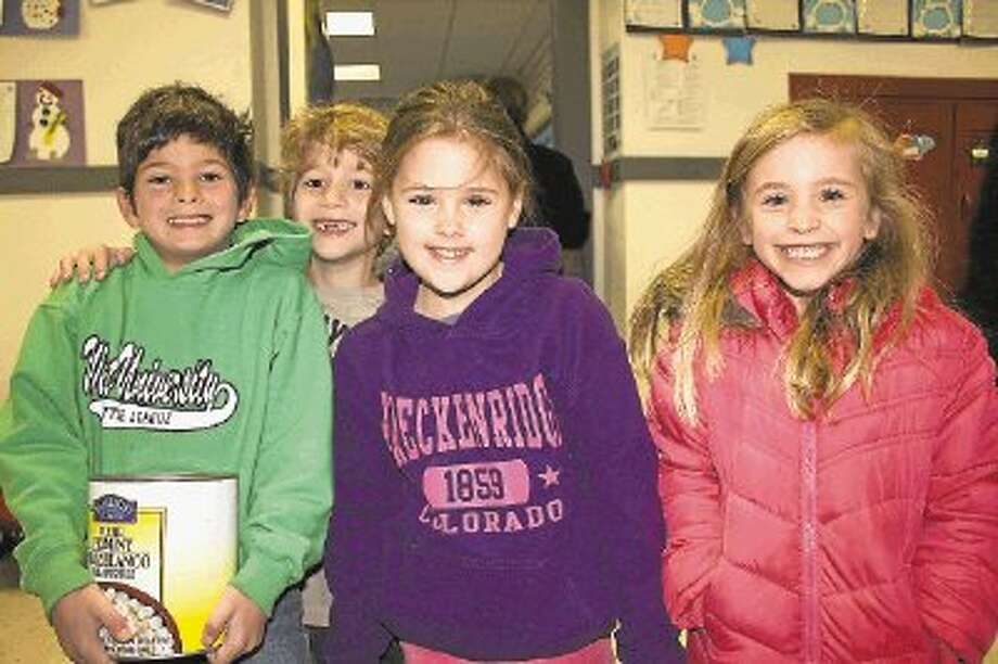 West University Elementary students Bailey Hashmi, Liam Gary, Elle Bradley, and Kendall Fisher with donations for the Souper Bowl of Caring during the school's week-long service project. The school was recognized last week for donating more than any other school in the nation. / @WireImgId=2663087