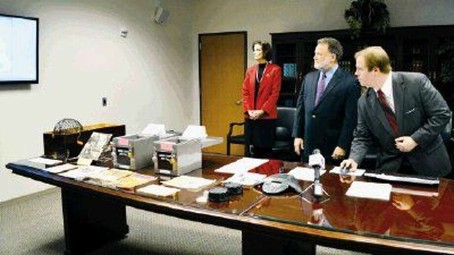 Harris County District Clerk Chris Daniel, right, presses a button and voila, the new jury wheel is launched with 2. 5 million names. State District Judge Sylvia Matthews, left, the head of the county's jury committee and state District Judge Robert Schaffer, the county's chief administrative judge, look on.