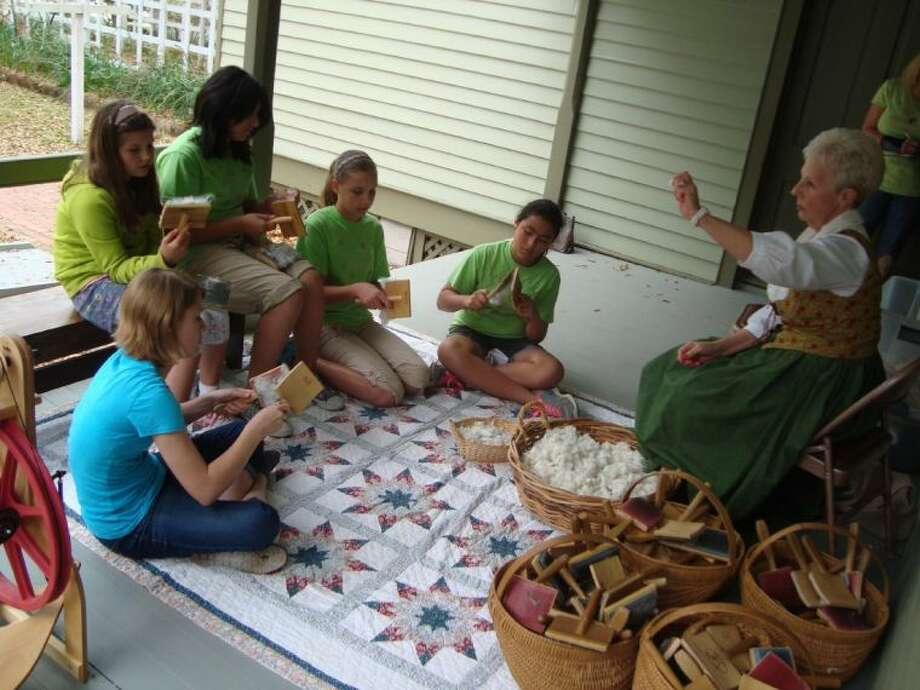 Docent President Austa Sue Kelley demonstrates cotton carding with Girl Scouts Kaylee Rogers, Ella Miller, Amaya Charez, Dinalia Miller and Sierra Hoffart. Photo: Photo Courtesy Fort Bend County