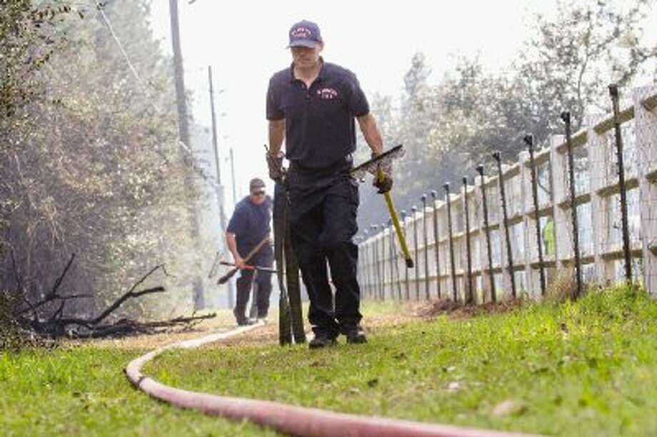The Magnolia Fire Department remove hoses near Towering Oaks street in the High Meadow Ranch subdivision at approximately 4 p.m. Thursday after responding to a runaway debris fire near Terri Lane and Goodson Loop that burned more than 20 acres before being contained. / The Conroe Courier