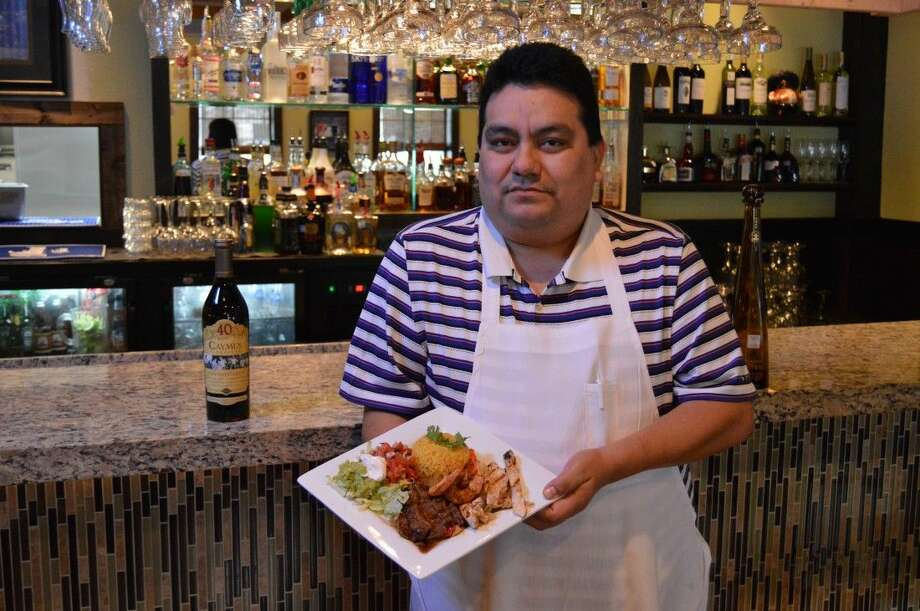 Rigo Luna showcases one of their signature meals in the newly expanded bar at Rigo's Kitchen in Kingwood.