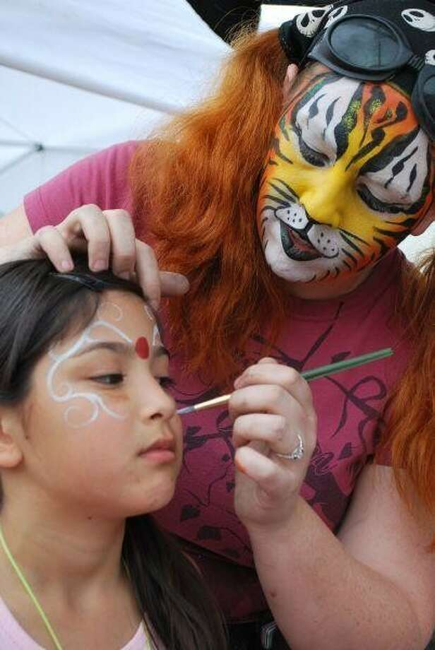 Tiffany Crosby paints intricate designs on the face of Mariah DelaCruz, 7, at a past Humble's Good Oil Days festival. Photo: STEFANIE THOMAS
