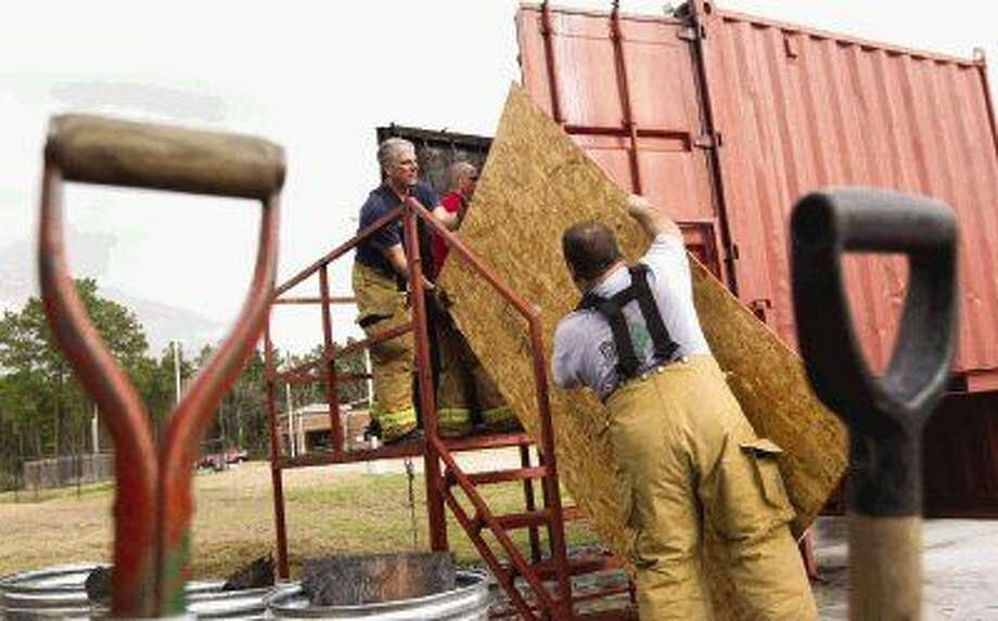 Fire training instructors load plywood into their new flashover fire chamber in The Woodlands Thursday. The chamber allows instructors to teach trainees about how a fire develops and various stages.
