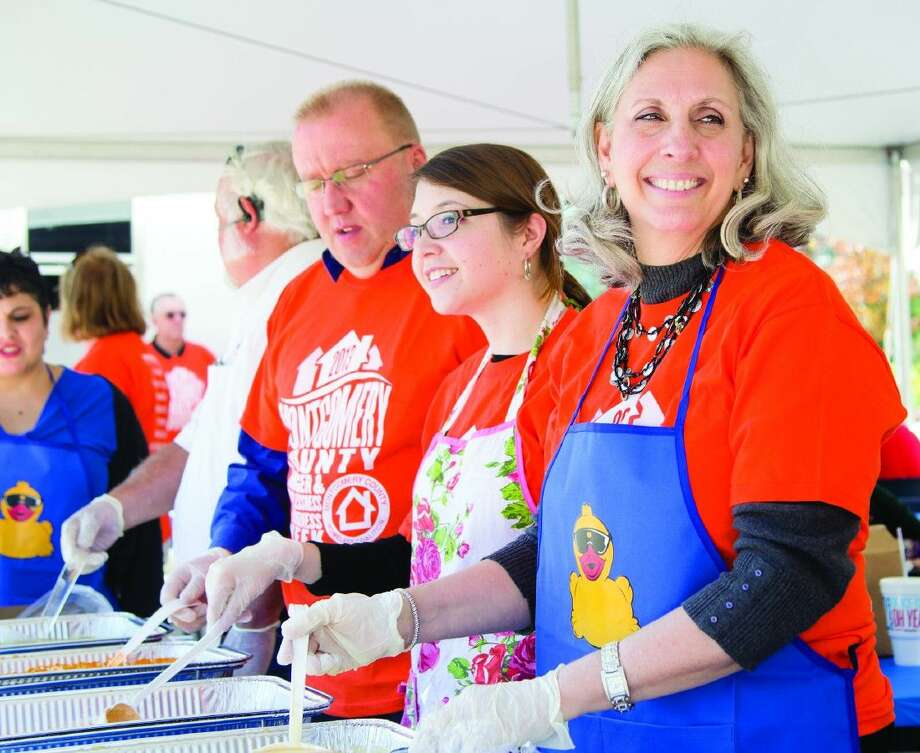 Pictured in this 2013 file photo, right, is President of Montgomery County United Way Julie Martineau serving at a soup line during Empty Bowls Luncheon in the parking lot of the Lone Star Family Clinic. Photo: Staff Photo By Ana Ramirez