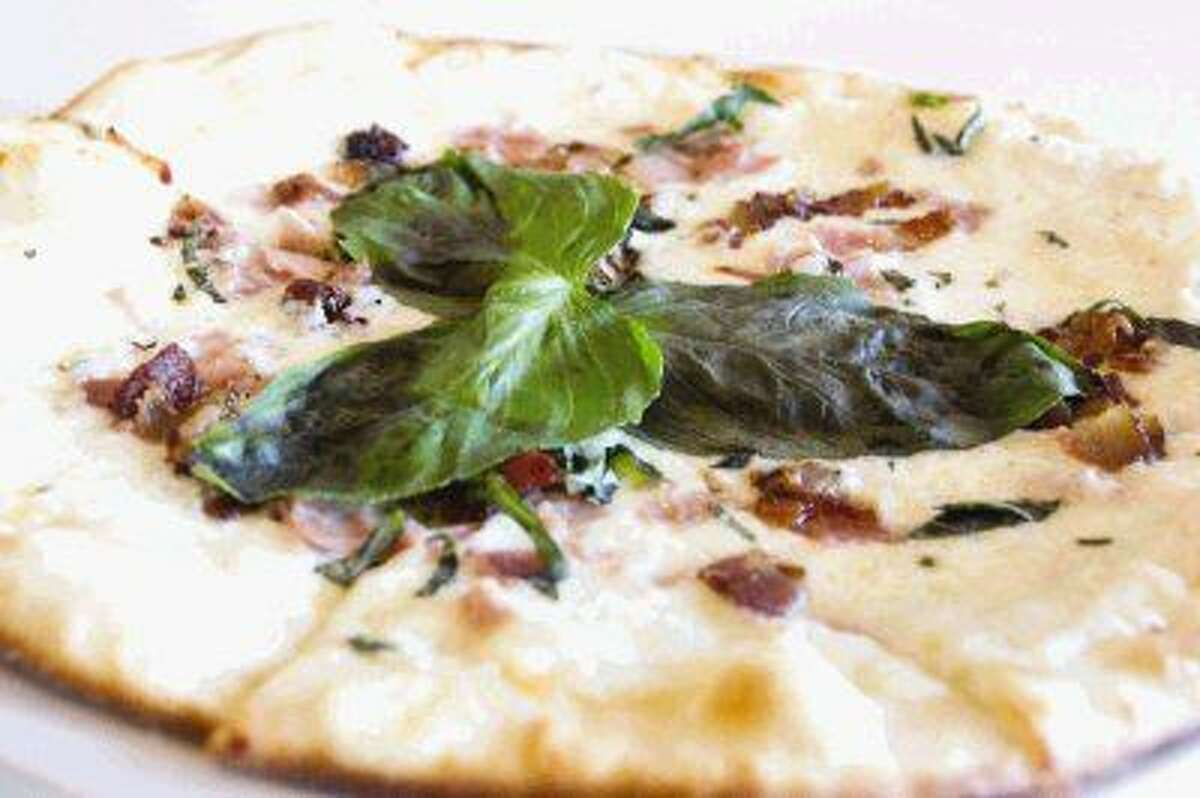 Ruggles Green, which recently opened in The Woodlands, serves a variety of foods, including the All-natural Ham and Bacon Wood-fired Pizza.