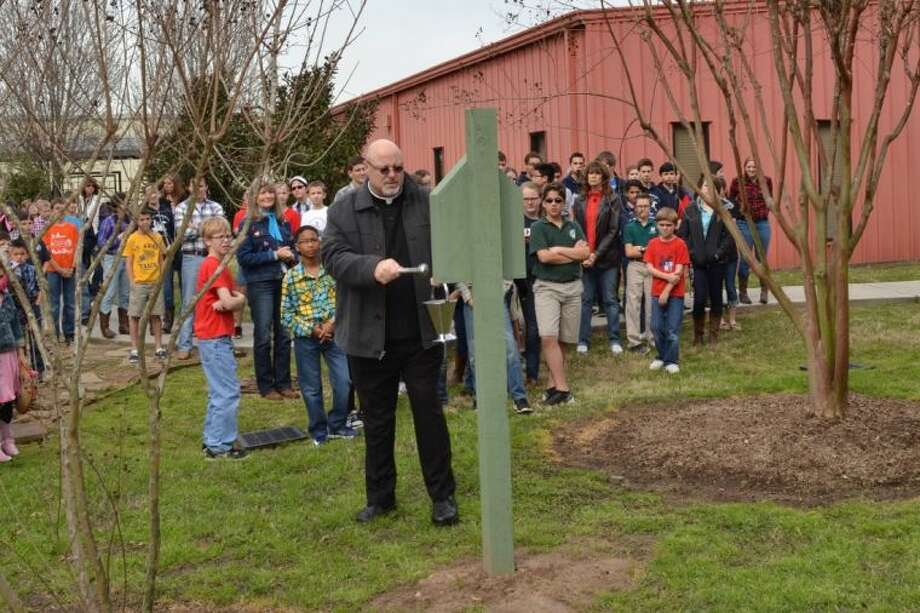 Father Tommy blesses the newly installed Stations of the Cross while St. Anne students look on. Photo: Submitted