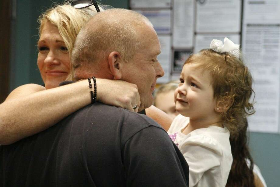 Lately Colletti and her mom, Carrie Shirley, give Humble paramedic Tom Miller a hug at the reunion celebration Feb. 1, 2015.
