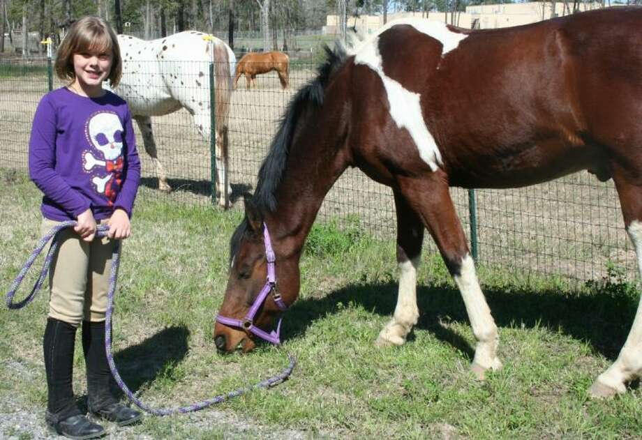 Emma Prather is one of several local children who have chosen New Caney's Big Horse Ranch of East Texas as their venue to learn to ride horses. Prather chose JD, one of the many horses available at the ranch, as her riding partner. Photo: STEPHANIE BUCKNER