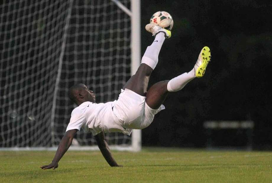 The Woodlands midfielder Bubacarr Jobe scores on a bicycle kick during a District 14-5A match against Bryan on Friday. Jobe scored four goals in the Highlanders' 9-1 win, which clinched their seventh straight league title. To view or purchase this photo and others like it, visit HCNpics.com.