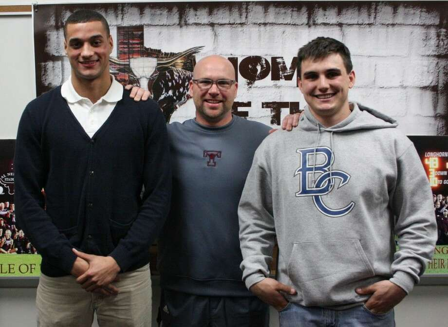 Tarkington ISD Athletic Director Brandon Carpenter (center) stands in between athletes Alex Latham (left) and Hunter Johnson (right) during their college signings on Feb. 4. Latham signed on to play football for the Kilgore College Rangers and Johnson signed on to play for the Blinn College Buccaneers. Photo: Jacob McAdams