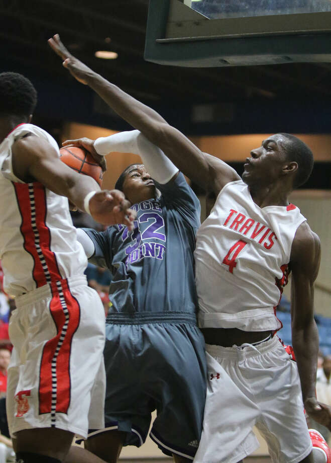 Ridge Point's Amir Smith drives against Travis' Hakeem Butler during their quarterfinal game in the Fort Bend Raising Cane's Basketball Tournament, Dec. 12 at Wheeler Field House in Sugar Land. Photo: Staff Photo By Alan Warren