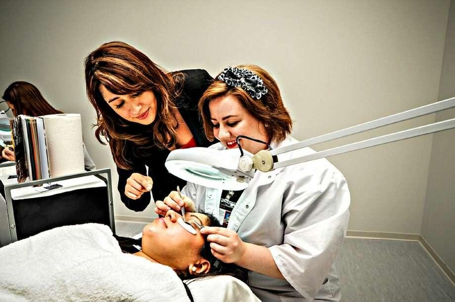 Instructor Aimee Rodriguez, left, watches as Jamie Vercell, a former LSC-Kingwood and LSC-North Harris student, carefully applies eyelash extensions on Cathy Rodriguez, a former LSC-North Harris student.