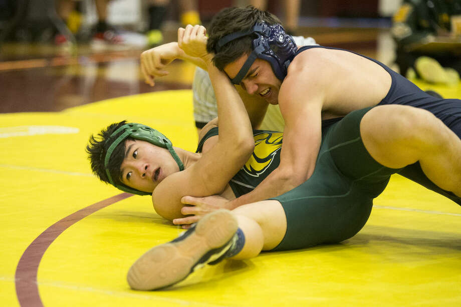 Kingwood's Matt Duncan pushes Klein Forest's Laun Nguyen to the edge of the ring during the District 9-6A Wrestling Championships on Feb. 5, 2015, at Summer Creek High School.