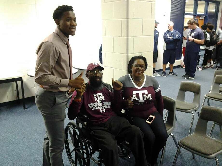 Cy Ridge receiver Kemah Siverand is pictured with his parents Wednesday. The wideout signed with Texas A&M. Photo: Adam Coleman