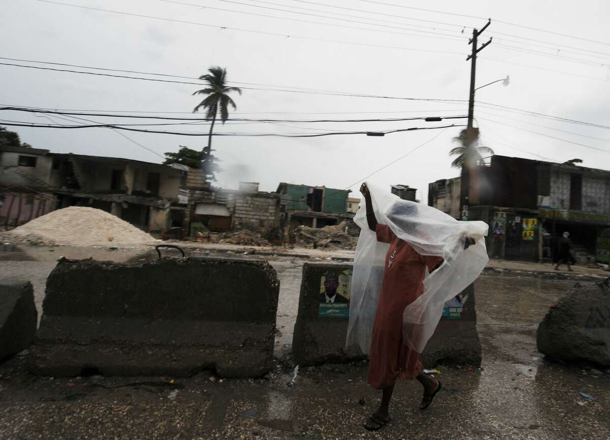 A woman walks under a cover in the rain Martissant, a slum area near Port-au-Prince on November 5, 2010. Heavy rains lashed Haiti Friday flooding one of the capital's largest refugee camps, triggering mud slides in the south, and leaving one person dead, local media and civil defense officials said. A makeshift camp for the homeless set up following the January quake which ravaged Port-au-Prince was already swamped after Hurricane Tomas began dumping rains over the country late Thursday. AFP PHOTO/Thony BELIZAIRE martissant (Photo credit should read THONY BELIZAIRE/AFP/Getty Images)