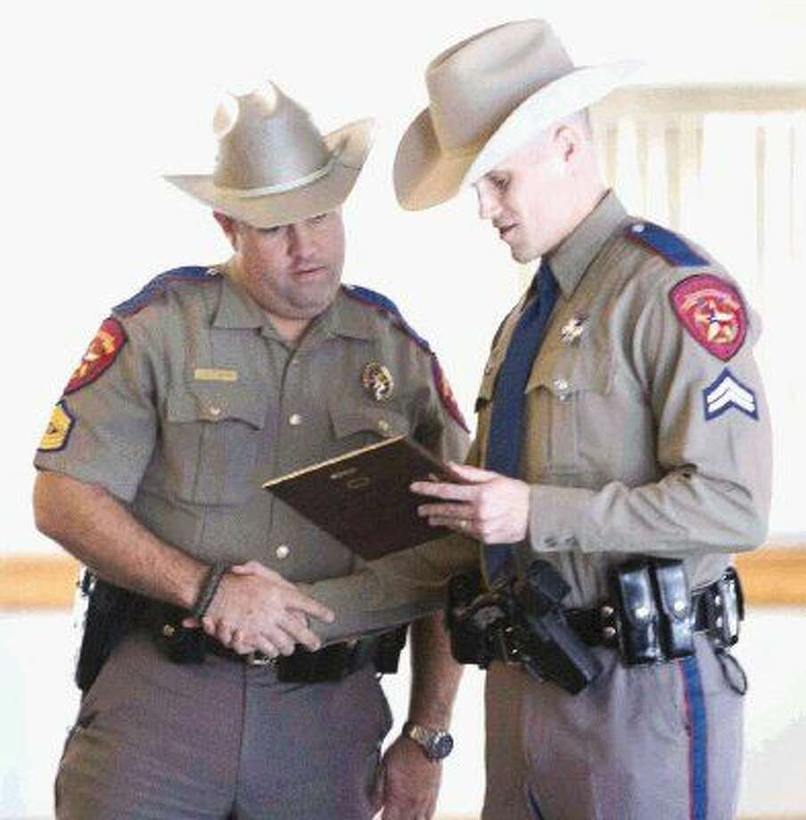 State Trooper Derek Leitner, left, congratulates fellow Trooper Sam Larson after Larson received the DWI Investigator of the Year award Wednesday at the Lone Star Convention and Expo Center. Photo: Jason Fochtman