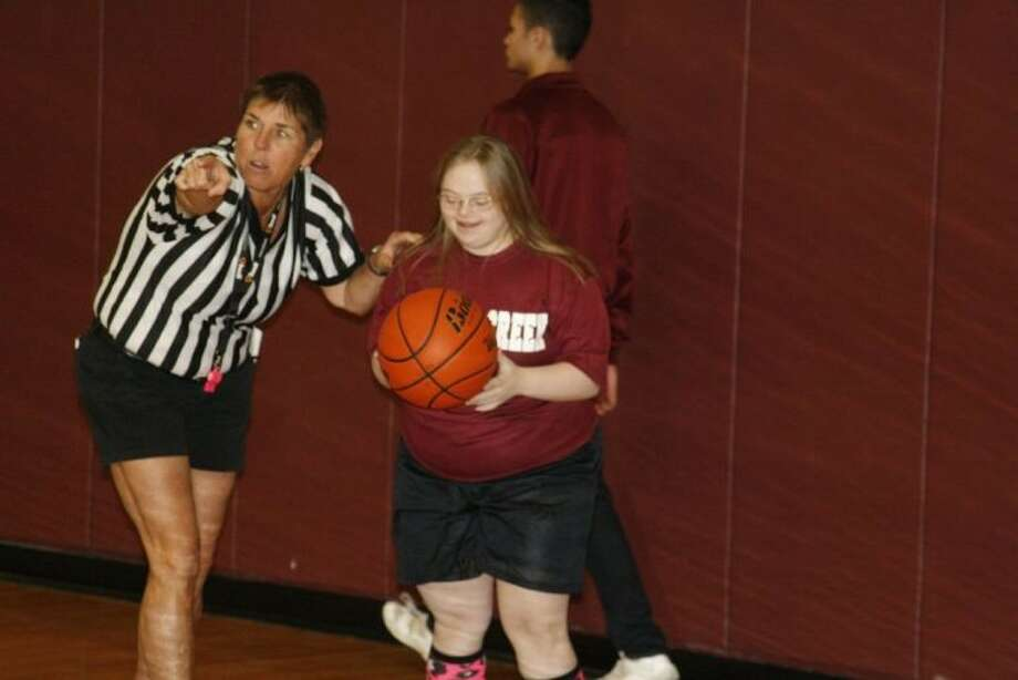 Summer Creek High School Special Education teacher Linda Lindsey helps a student throw the basketball back in bounds during the District-wide Integrated PE Basketball Game between students from Summer Creek, Atascocita, Kingwood and Kingwood Park High Schools Jan. 17, 2014.