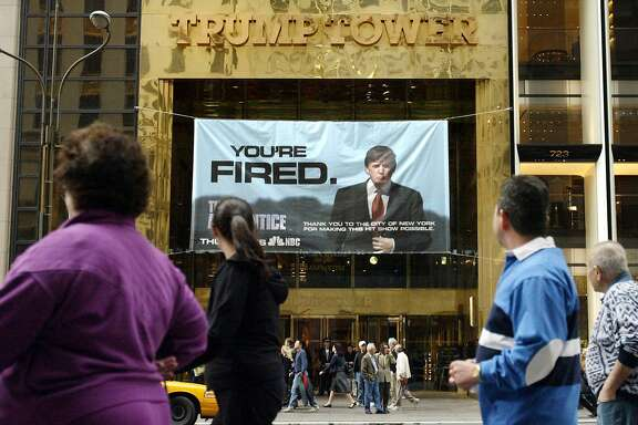 """FILE - In this Saturday, March 27, 2004 file photo, passersby look at a sign advertising the reality television show, """"The Apprentice,"""" displayed at the entrance to the Trump Tower building in New York. Donald Trump's development firm was issued summonses by the city because it did not have the proper permits for the giant banner. In his years on the show, Trump repeatedly demeaned women with sexist language, according to show insiders who said he rated female contestants by the size of their breasts and talked about which ones he'd like to have sex with. (AP Photo/Bebeto Matthews)"""