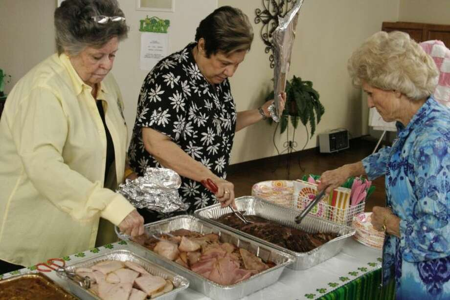 Carolyn Coats, Vera Nykaza and Juanita Stegall help set up the food for guests at the Good Oil Days Sponsor Appreciation Luncheon March 20, 2014.