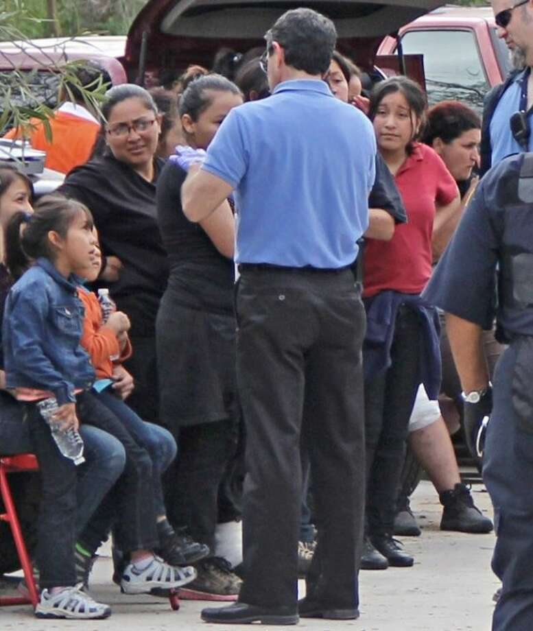 Police rescued 95 men and 15 women, including a pregnant woman and two young children from a small house in a rural area less than three miles from Nolan Ryan Junior High. The captives emerged from the house hungry, thirsty and scared after investigators raided the property Wednesday (March 19). Photo: KRISTI NIX