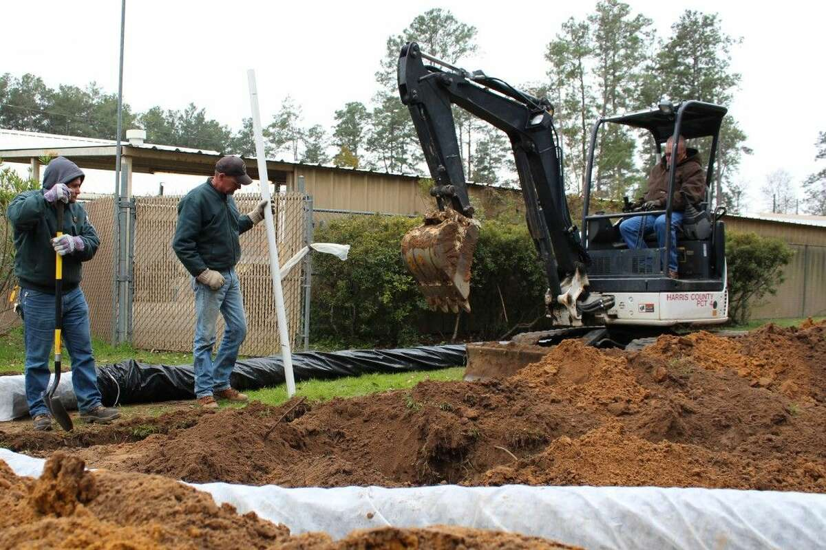 Parks staff John Urrey, Keith Emshoff, and Tommy Simms work to expand storage at Burroughs Park.
