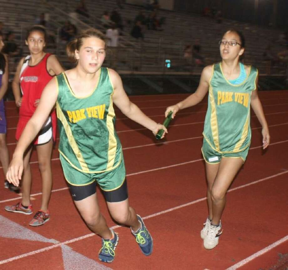 Two Park View relay team members complete the handoff during the 4 by 400 relay race Wednesday night. Photo: Robert Avery